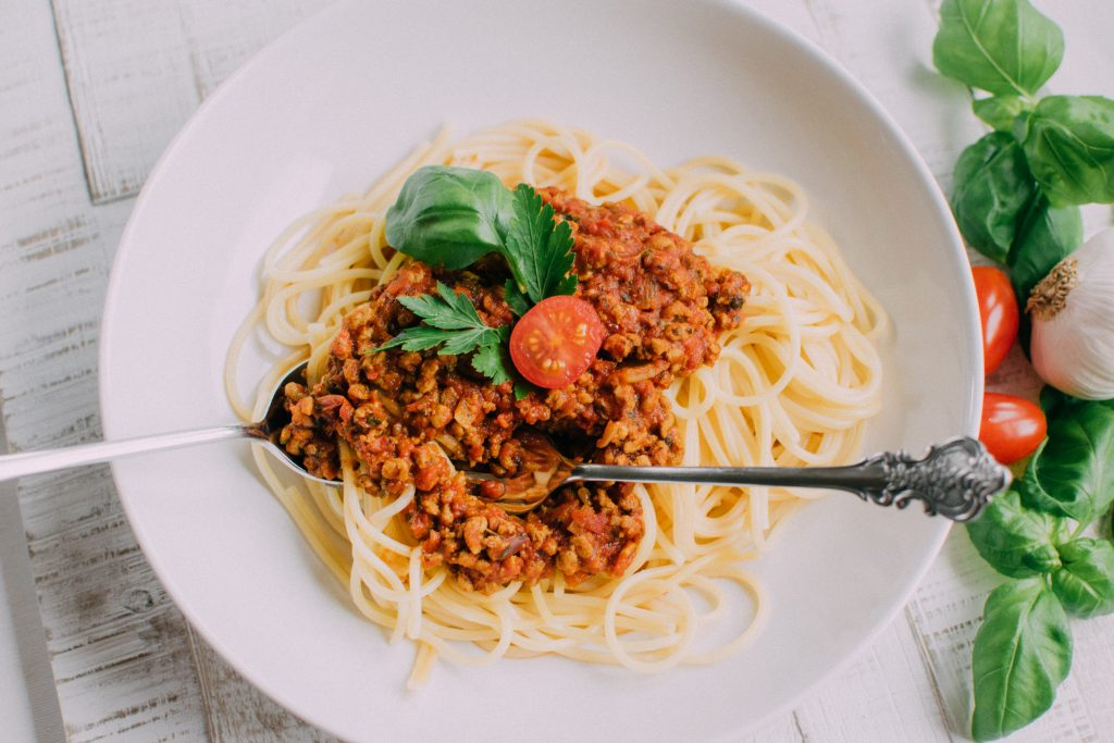 SunflowerFamily Pasta Bolognese in a white bowl with a tomato, parsley, and basil garnish.