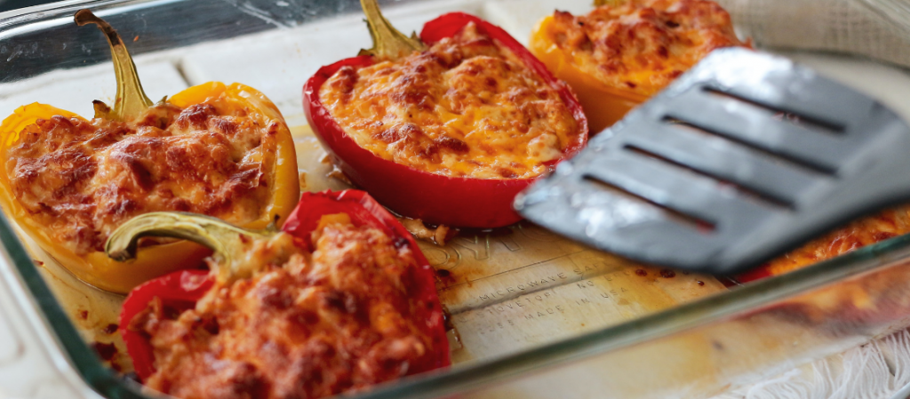 Bell peppers stuffed with sunflower haché and melted cheese in a baking dish with a spatula.