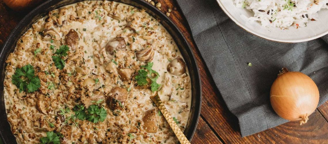 Pan of creamy mushroom stew and rice on a wooden table.