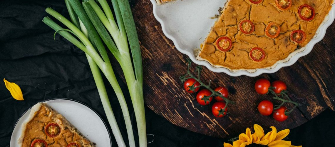 Vegan Quiche filled with Sunflower Hache on a wooden table with a slice on a plate and decorative sunfowers.