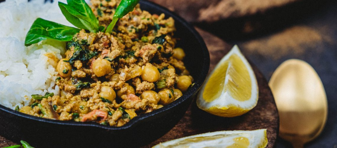 Cast iron skillet filled with rice and Indian Chana Dal with two lemon slices on the side.