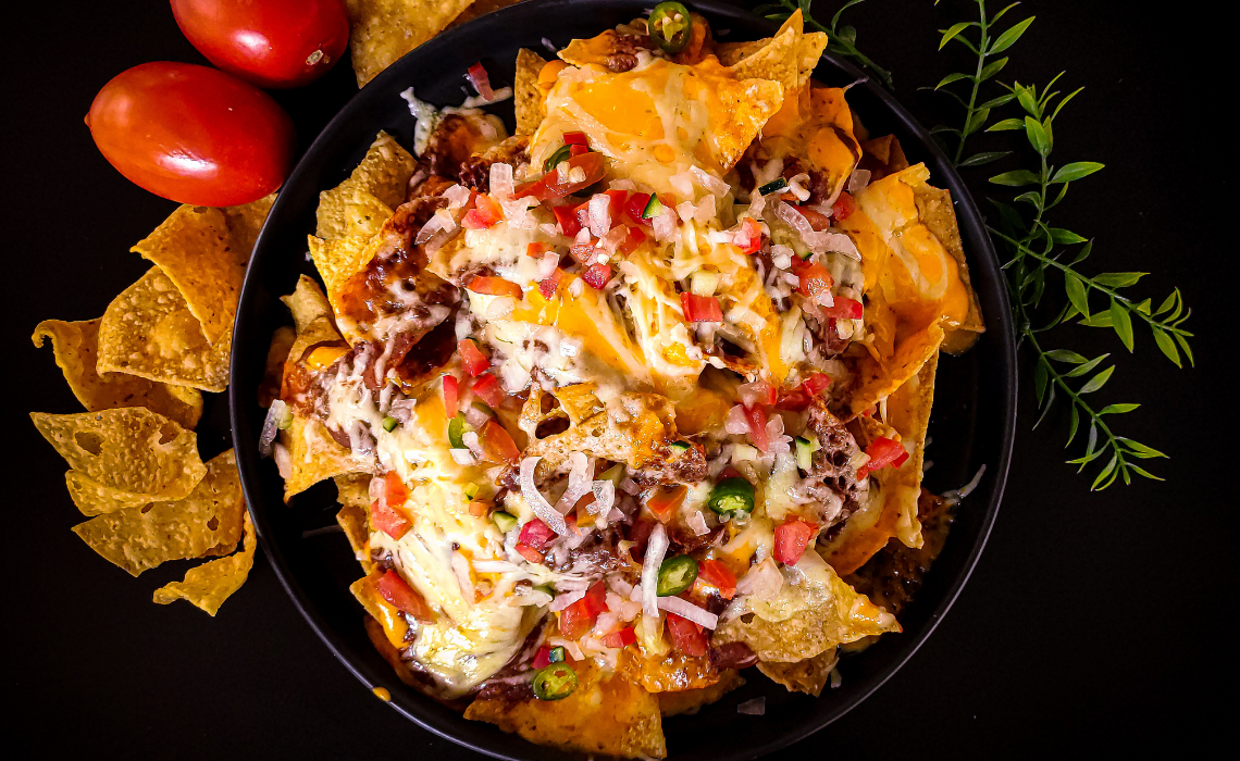 Meatless nachos with cheese and toppings on a black plate with a black background surrounded by chips, tomatoes, and green garnishes.
